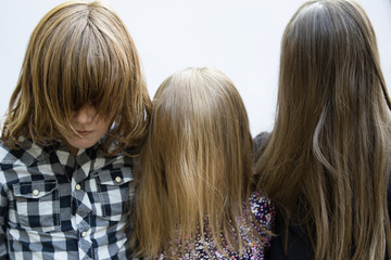 Portrait of kids with hair covering faces on white background