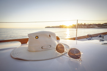 Close up of hat and sunglasses on boat over sea against clear sky during sunset