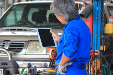 Car mechanic holding digital tablet in auto repair service.