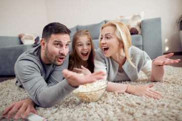 Family lying on the floor, watching TV together