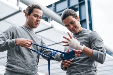 Identical male adult twin boxers training outdoors, bandaging hands with hand wraps