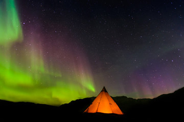 Lit up tent, Aurora Borealis in background, Narsaq, Vestgronland, Greenland