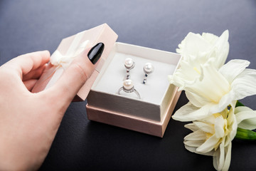 Woman opens gift box with pearl jewellery. Set of earrings and ring with flowers as a present for Mother's day.