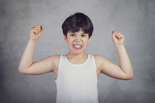 niño fuerte que enseña sus músculos sobre fondo gris