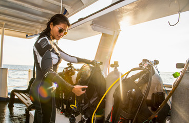 Woman checking diving equipment on ship