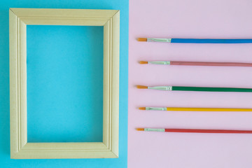 Photo frame with multicolored paint brushes on pastel background