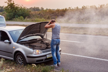 A young man in despair clutched his head, because his car broke down on the road and it is not possible to repair it. Smokes from under the hood.