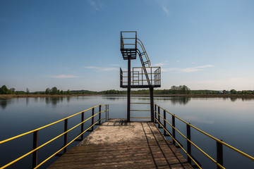 silhouette of diving tower on the lake in summer evening