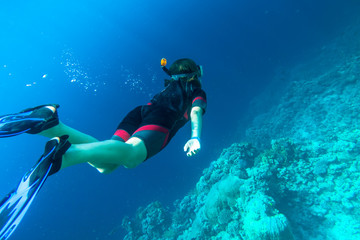 Girl in snorkeling gear dives into the sea