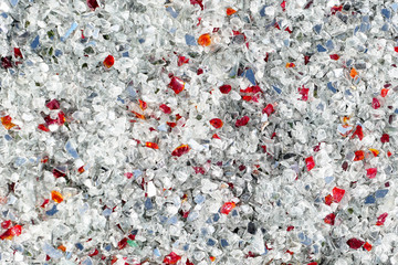 white broken glass full frame background. red pieces among. recycling process