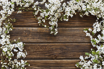 Close-up photo of Beautiful white Flowering Cherry Tree branchesheart shape on vintage wooden background.  Wedding, engagement or betrothal concept. Top view, greating card.