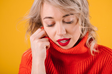 Relaxed thoughtful romantic blobde woman portrait in red jumper. Yellow background. stressed