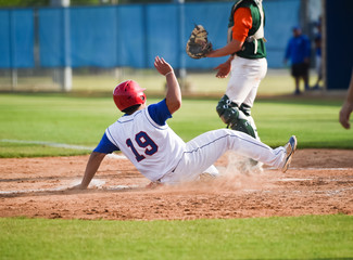 Baseball player sliding into the base during a game