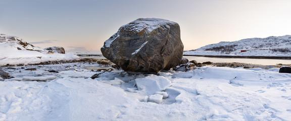 Snowy coast on Norwegian fiord with rock, Lapland