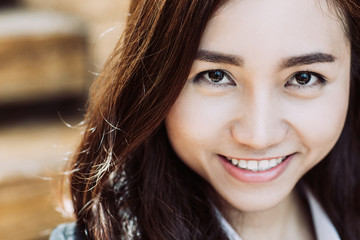 Close up portrait of smiling young Asian businesswoman looking at camera