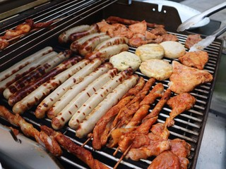 Various assorted meat on a grill. Grilling season concept. Sausages, meat rolls, grilled tofu. Delicious eating. Top view, close up