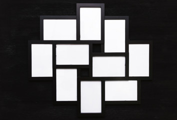 Blank photo picture frame isolated on black wooden board background.