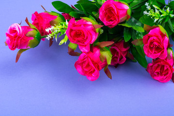 Artificial roses on lilac background