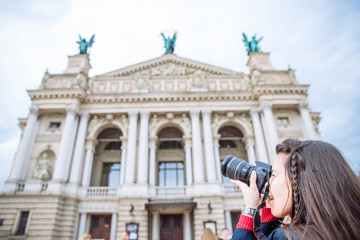 tourist woman taking picture of old european building. travel concept. copy space