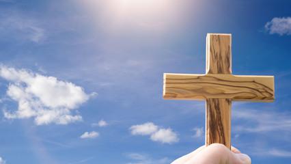 Hand hält Holzkreuz in den Himmel