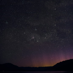 Night picture of a minimal landscape of the stars and Southern Cross in New Zealand. The purple, yellow, red and orange lights emerging behind the mountains came from Queenstown.