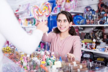 Smiling girl buying sweet candy from seller in shop