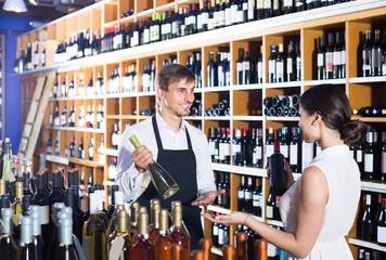 portrait of male seller  showing bottle of wine to female customer in wine shop