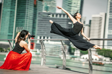 Two beautiful young girls having fun photo shooting on a deck with skyscrapers city background