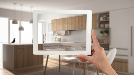 Hand holding tablet showing real finished minimalist white and wooden kitchen. Modern blurred kitchen in the background, architecture interior design presentation