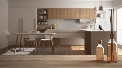 Wooden table top or shelf with aromatic sticks bottles over blurred modern minimalistic kitchen, white architecture interior design