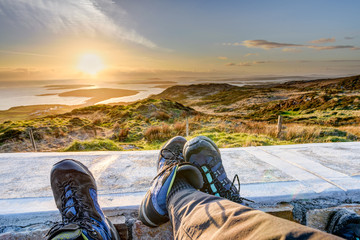 Two people in hiking shoes are enjoying scenic view of the sunset over the Clifden Bay in Ireland in place called the Sky Road