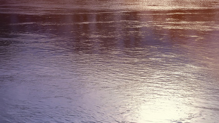 water surface with ripples. Reflection of the sun. natural background.