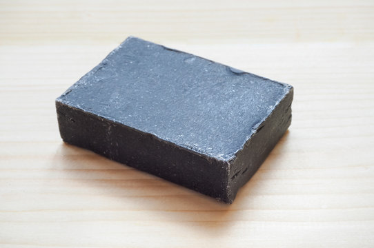 Block of natural black carbon soap on wooden background.