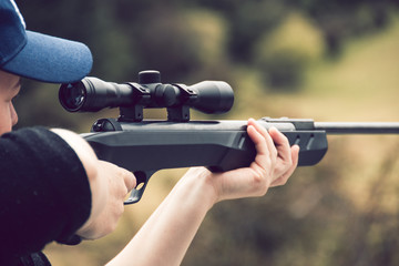 Young woman shooting rifle on farm
