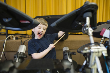 Playful boy playing drum kit at Grace Baptist Church