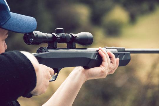 Young woman shooting rifle on farm