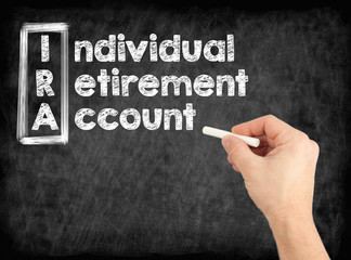 IRA - Individual Retirement Account concept. Hand writing by white chalk on a blackboard.