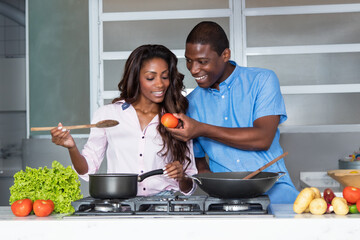Happy african american love couple cooking at kitchen