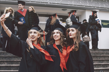 Happy female friends wearing graduation gowns taking selfie while standing on steps