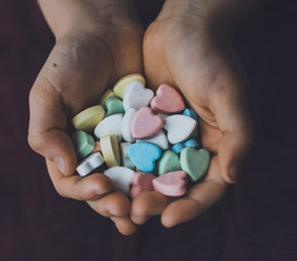 Cropped hands of boy holding colorful heart shape candies at home