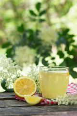 Home-made refreshing healthy summer elderberry (Sambucus) juice, vertical. Elderberry flower in background.