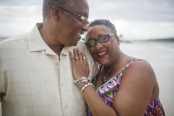 Happy senior couple standing at beach