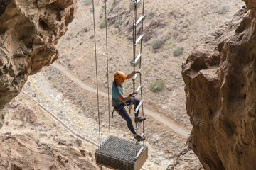 Female hiker climbing on rope ladder amidst mountains