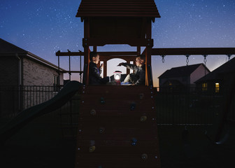 Brothers with illuminated lantern sitting on outdoor play equipment against star field at park