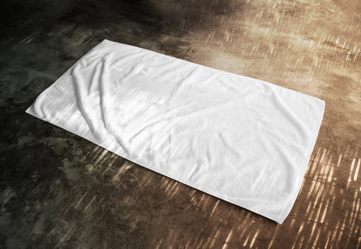 Blank white beach towel mockup on textured floor, side view. Clear unfolded wiper mock up lying on the surface. Shaggy fur bath rug