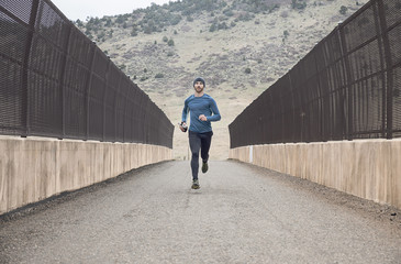 Man running on bridge against mountain