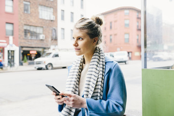 Young woman looking away while using smart phone in city