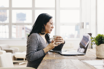 Businesswoman holding coffee cup while using laptop in office