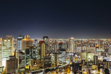 High angle view of illuminated cityscape against clear sky at night