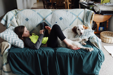 Girl using tablet computer while lying on sofa with dog at home